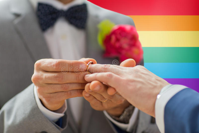 Close up of male gay couple hands and wedding ring. People, homosexuality, same-sex marriage and love concept - close up of happy male gay couple hands putting royalty free stock photo