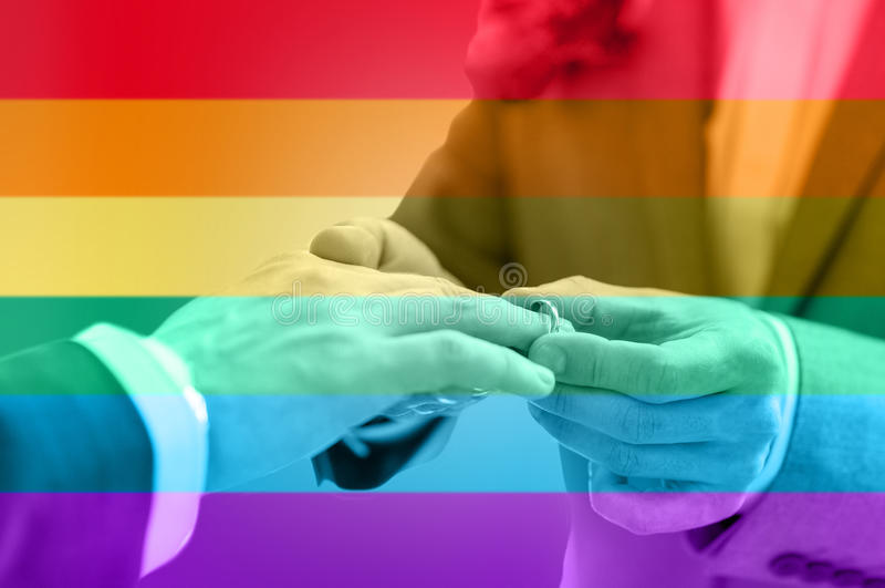Close up of male gay couple hands and wedding ring. People, homosexuality, same-sex marriage and love concept - close up of happy male gay couple hands putting stock images