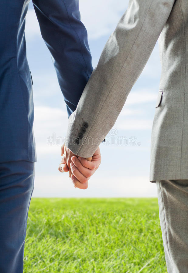 Close up of male gay couple holding hands. People, homosexuality, same-sex marriage and love concept - close up of happy male gay couple holding hands from back stock photo