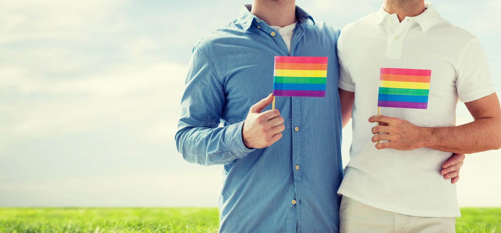 Close up of male gay couple holding rainbow flags. People, homosexuality, same-sex marriage, gay and love concept - close up of happy male gay couple hugging and royalty free stock photography