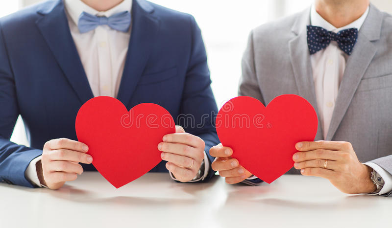 Close up of male gay couple holding red hearts. People, homosexuality, same-sex marriage, valentines day and love concept - close up of happy married male gay stock images