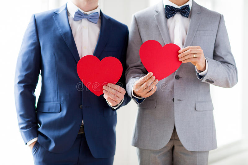 Close up of male gay couple holding red hearts stock images