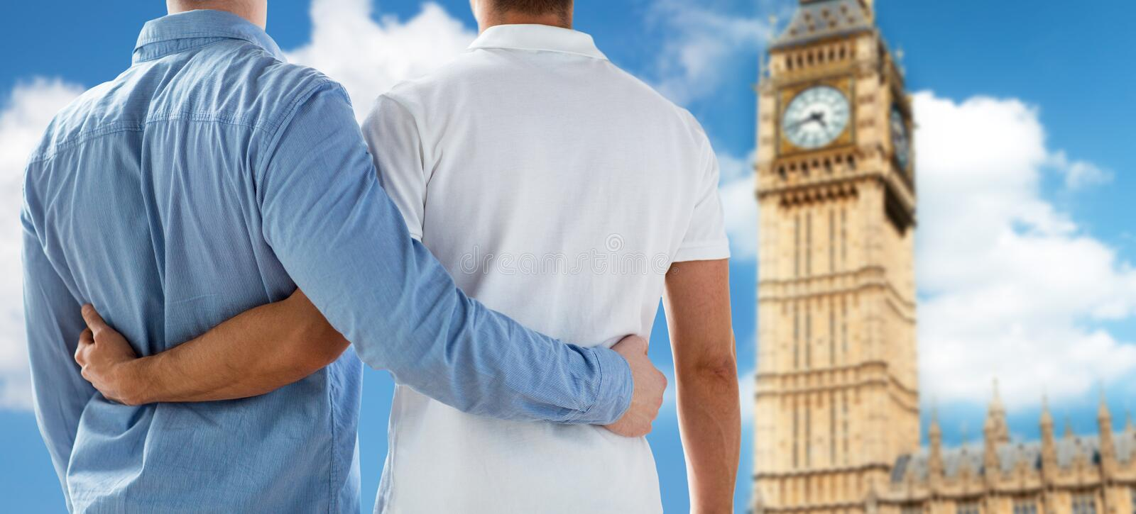 Close up of male gay couple hugging over big ben. People, homosexuality, same-sex marriage, travel and love concept - close up of happy male gay couple hugging stock photography