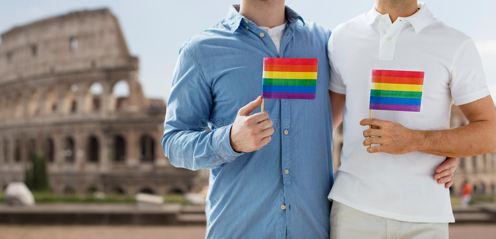 Close up of male gay couple with rainbow flags. People, homosexuality, same-sex marriage, travel and love concept - close up of happy male gay couple holding royalty free stock photo