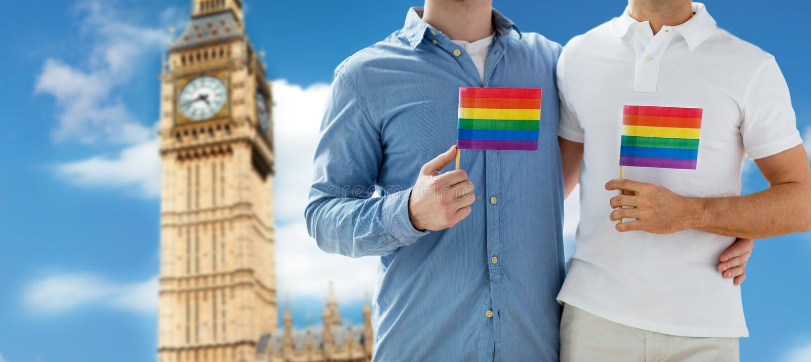 Close up of male gay couple with rainbow flags. People, homosexuality, same-sex marriage, travel and love concept - close up of happy male gay couple holding royalty free stock photography