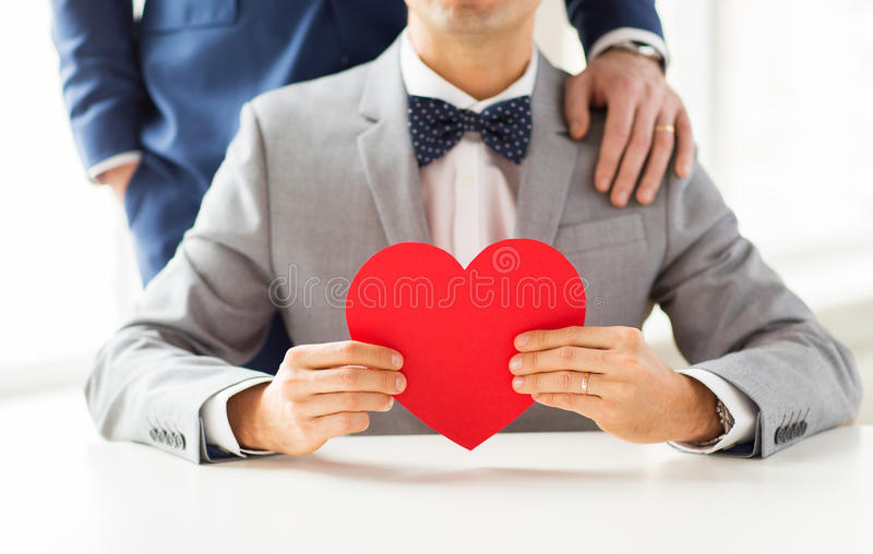 Close up of male gay couple with red heart. People, homosexuality, same-sex marriage, valentines day and love concept - close up of happy married male gay couple stock image