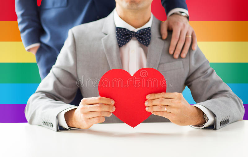 Close up of male gay couple with red heart. People, homosexuality, same-sex marriage, valentines day and love concept - close up of happy married male gay couple royalty free stock photos