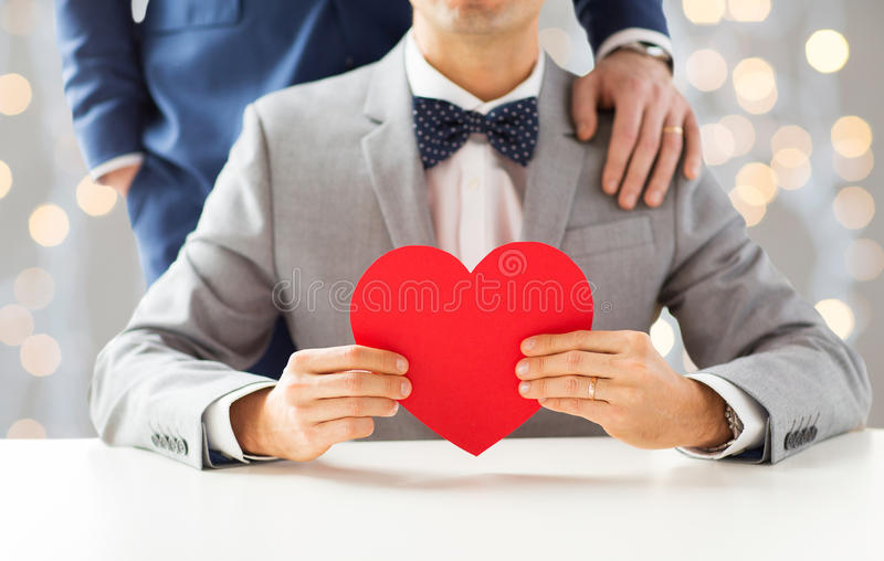 Close up of male gay couple with red heart. People, homosexuality, same-sex marriage, valentines day and love concept - close up of happy married male gay couple royalty free stock image
