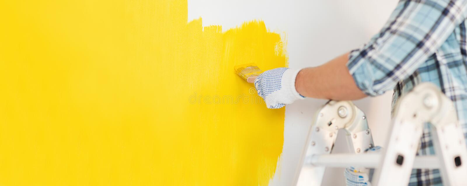 Close up of male in gloves painting a wall stock images