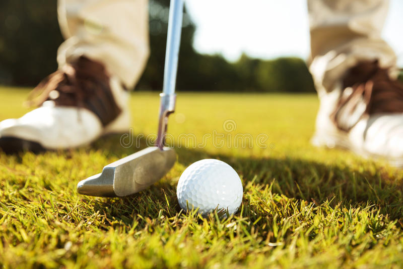 Close-up of male golfer teeing off. While standing on golf course stock photography