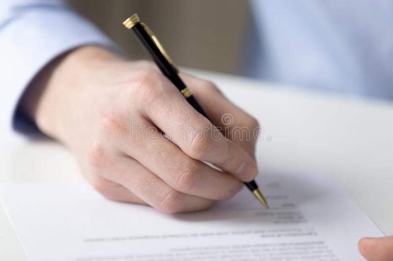 Close up male hand fill contract paper. Customer sitting at table holds pen filling contract official document buy or sell property getting insurance or affirms royalty free stock photos