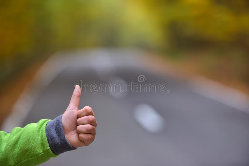Close up of male hand hitchhiking, waiting a coming car for a ri stock photo