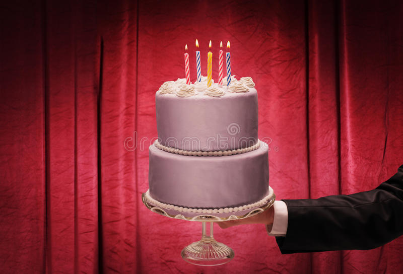 Close-up on a male hand holding a birthday cake. In front of a red curtain stock photography