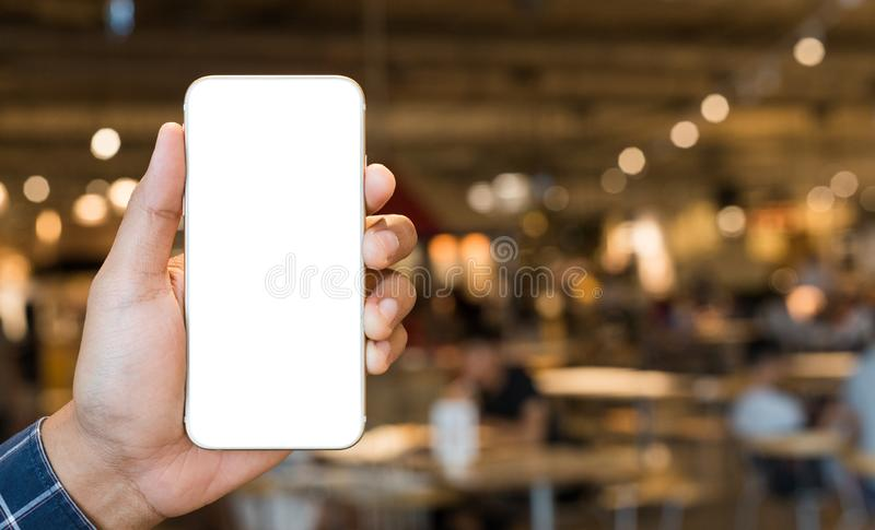 Close up male hand holding smartphone blank screen on park background. stock photography