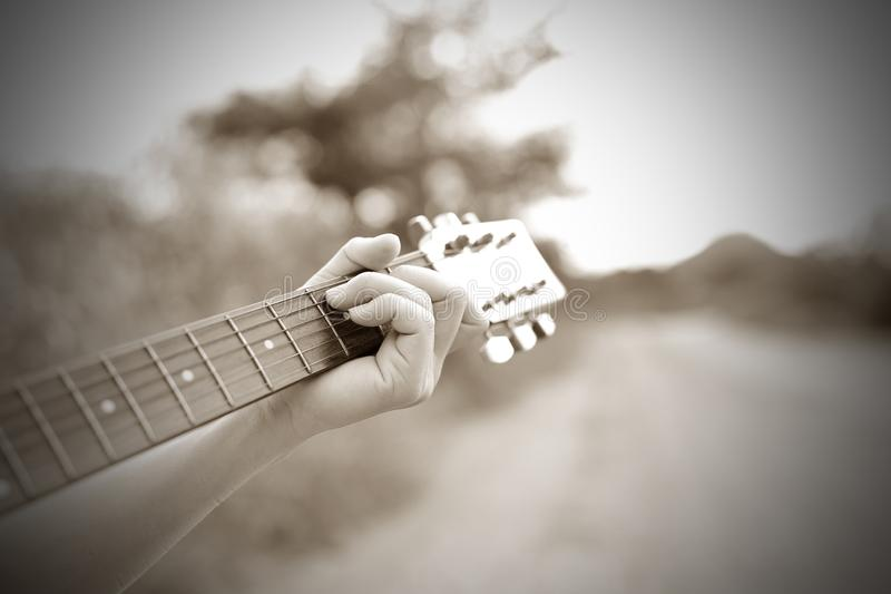 Close-up male hand playing on acoustic guitar outdoor. Vintage tone.  royalty free stock photography
