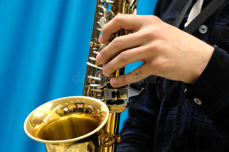 Close-up of a male hand playing a musician on a gold saxophone on a blue background. Theme for music news. stock photography