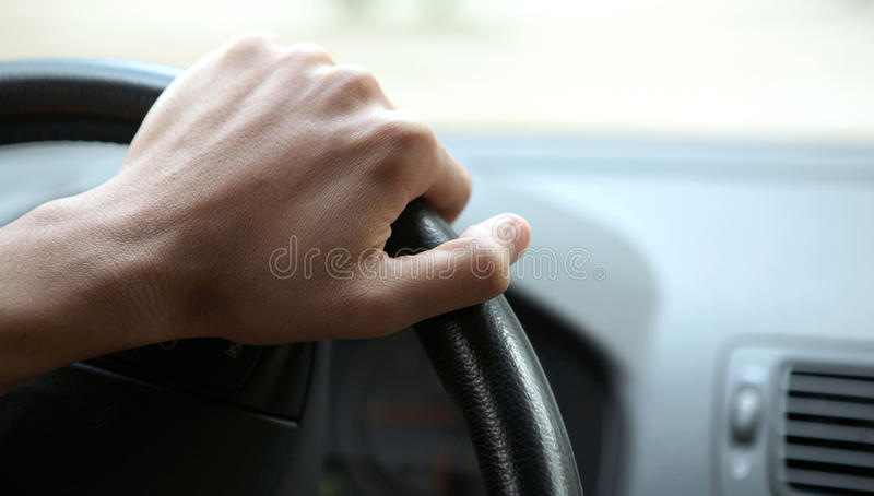 Close-up of a male hand on steering wheel royalty free stock photos