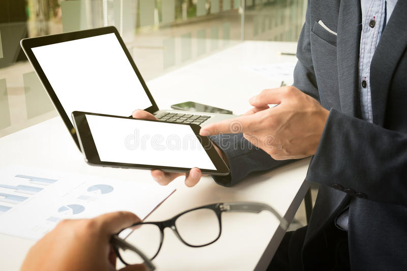 Close-up of male hand, using tablet and computer laptop while si stock photos
