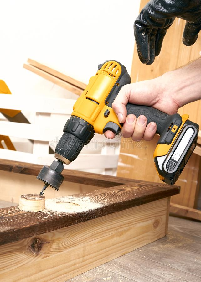 Close-up of a male hand and a yellow screwdriver. A man makes a big hole in the board with a special tool. royalty free stock photo