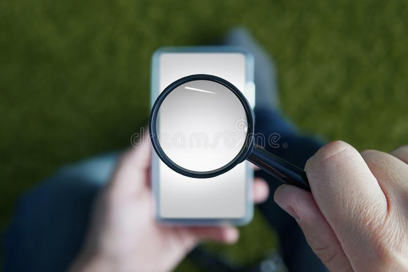 Close up of male hands holding smartphone with magnifying glass above the device screen. Shot of a sitting person with royalty free stock image
