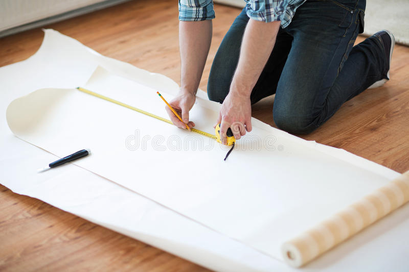 Close up of male hands measuring wallpaper. Repair, building and home concept - close up of male hands measuring wallpaper stock photography