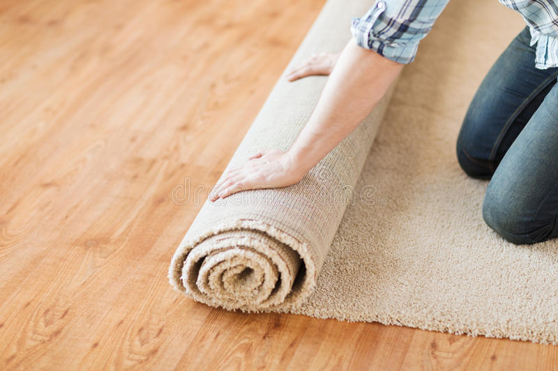 Close up of male hands unrolling carpet. Repair, building and home concept - close up of male hands unrolling carpet royalty free stock photos