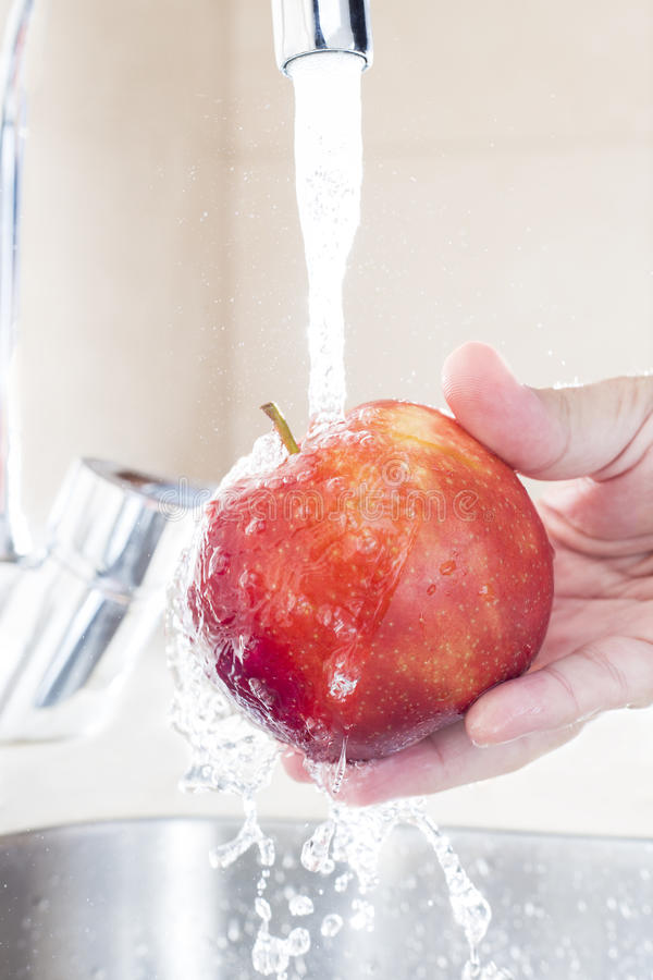 Close up male hands washing apple under water in sink royalty free stock image