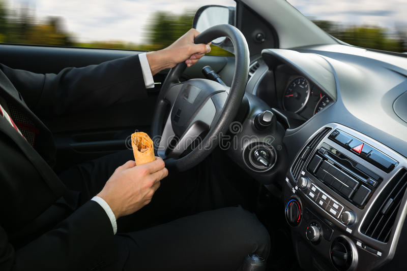Close-up of a male holding snack while driving royalty free stock images