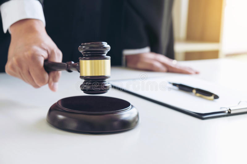 Close up of Male lawyer or judge hand's striking the gavel on so stock image