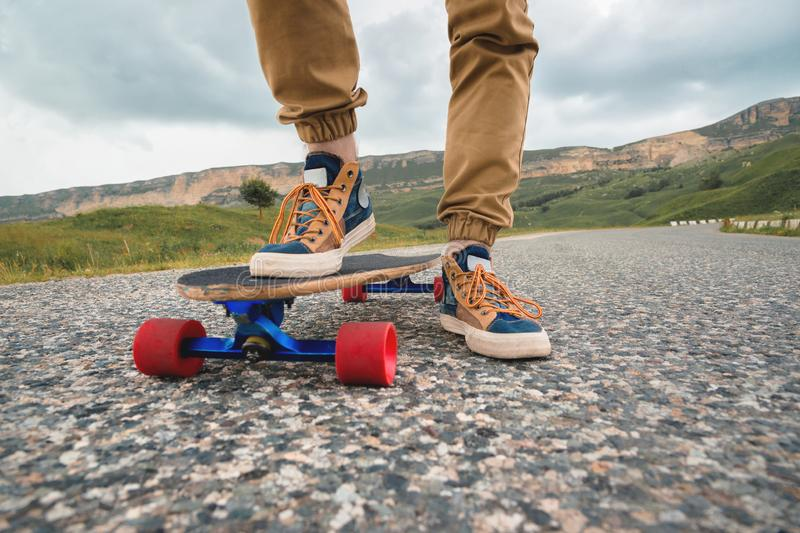 Close-up of male legs in rag sneakers on a longboard on the background of asphalt at sunset. Big skateboard with man. Legs. Youth leisure concept stock image