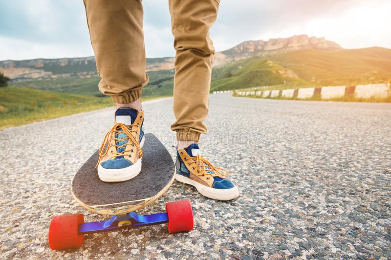 Close-up of male legs in rag sneakers on a longboard on the background of asphalt at sunset. Big skateboard with man. Legs. Youth leisure concept stock photo
