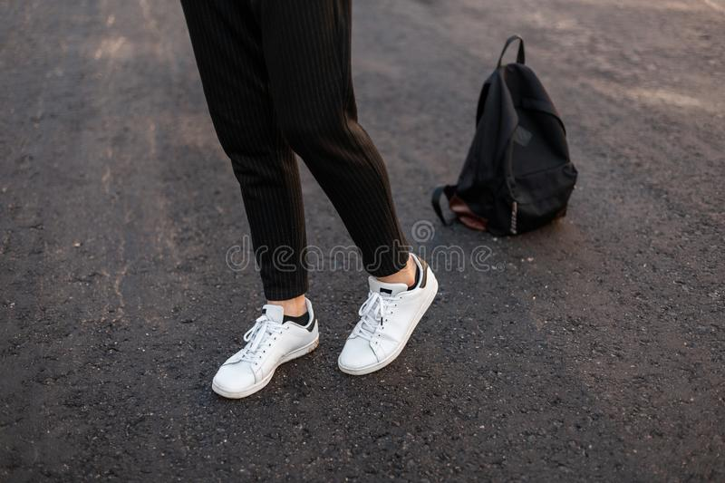 Close-up of male legs. Young fashionable guy in vintage black pants in leather stylish white sneakers posing standing. On the pavement against a black backpack stock images