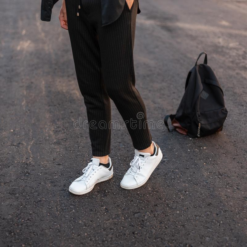 Close-up of male legs. Young fashionable guy in vintage black pants in leather stylish white sneakers posing standing. On the pavement against a black backpack royalty free stock photos