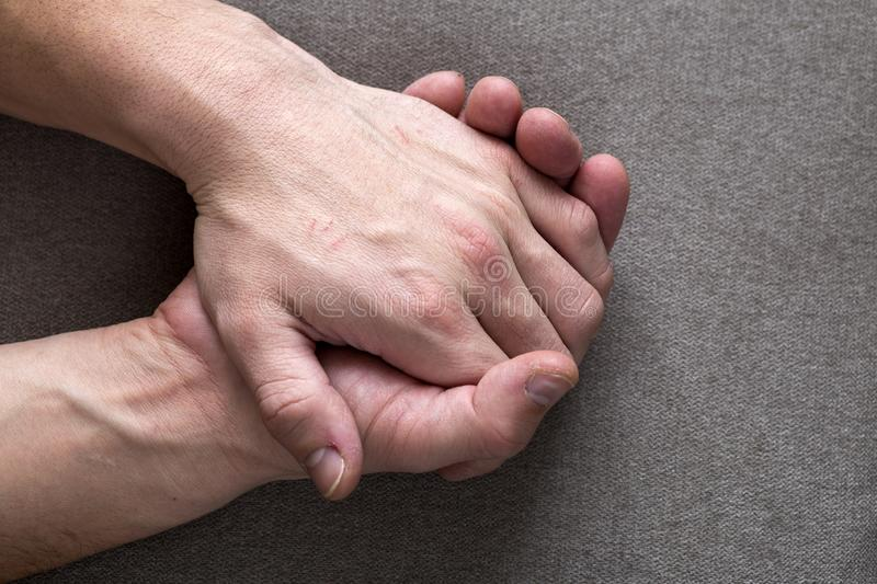 Close-up of male masculine young worker hands with rough skin and short fingernails resting on flat copy space background, top stock image