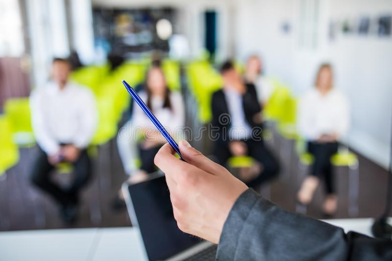 Close up of male mentor or coach hold paperwork, give flipchart presentation, talking with employees. Businessman have stock photos