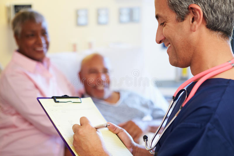 Close Up Of Male Nurse Updating Patient Notes. Wearing A Stethoscope Around Neck stock photo