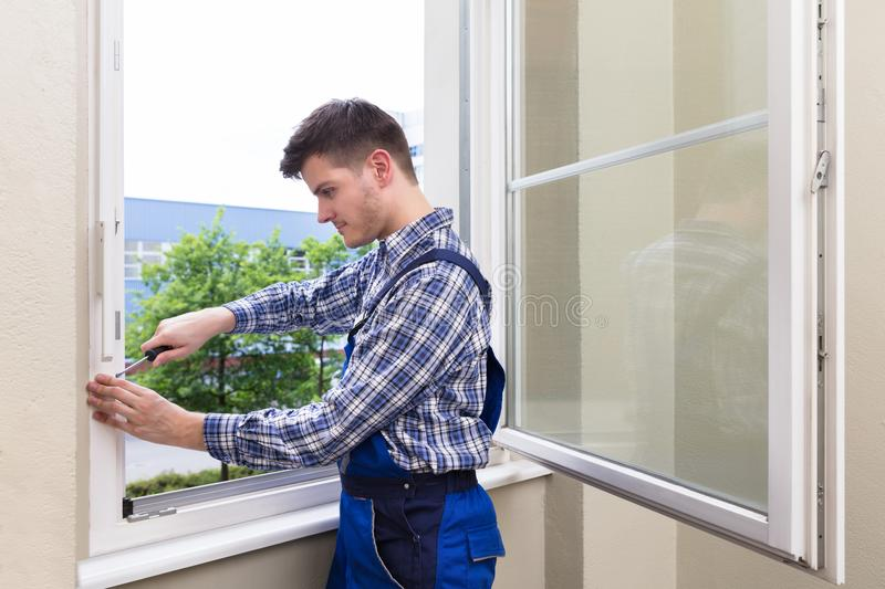 Repairman Fixing Window With Screwdriver stock photos