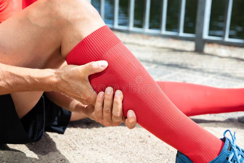 Runner Suffering From Pain In Calf Muscle. Close-up Of A Male Runner Suffering From Pain In Calf Muscle stock images