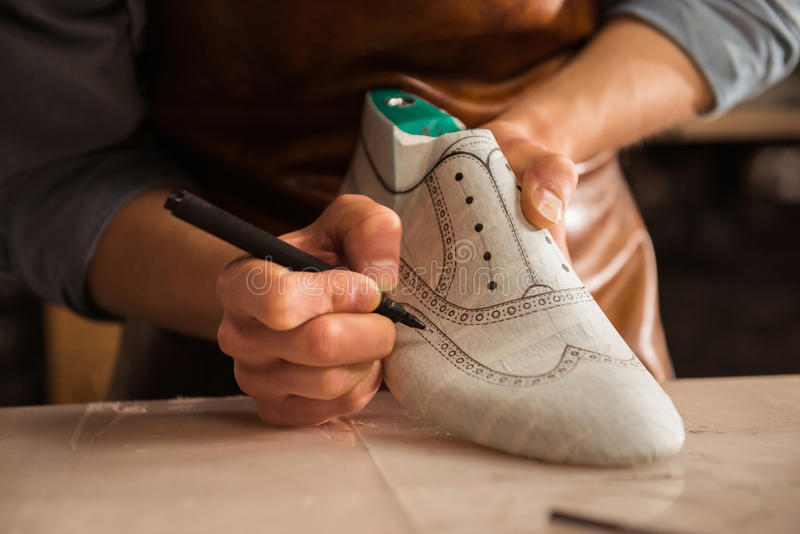 Close up of a male shoemaker drawing design. On a new shoes at his workshop stock photography