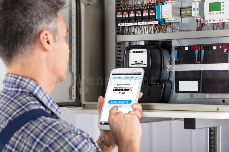 Technician Doing Meter Reading Using Mobilephone stock photos