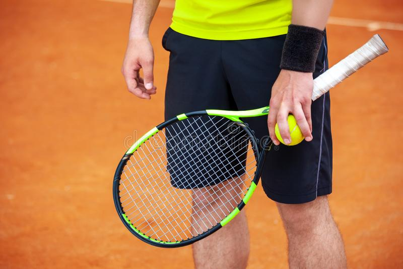 Closeup male tennis player holding racket and ball stock photo