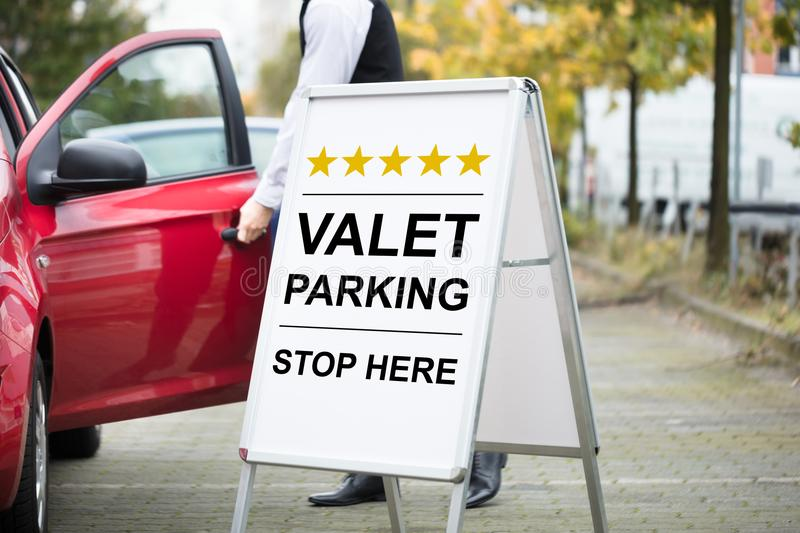 Young Male Valet Standing Near Valet Parking Sign royalty free stock images