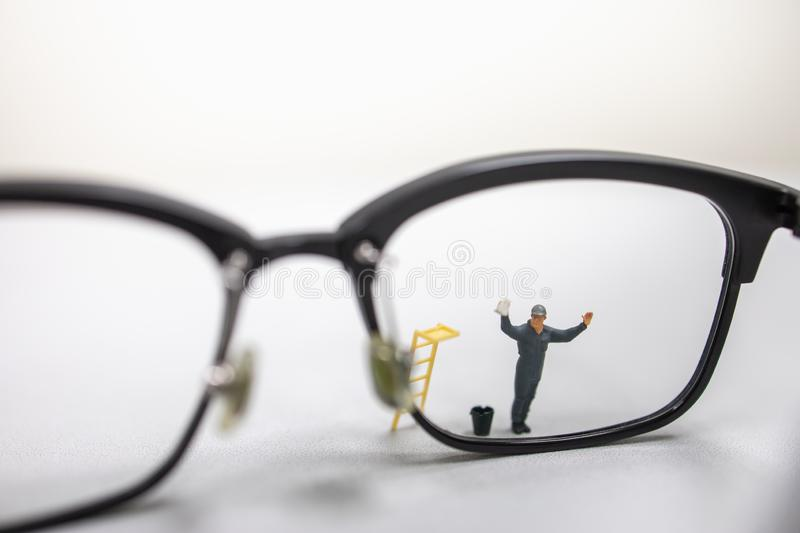 Close up of male worker miniature figure wipe and clean a dirty reading glasses with bucket and ladder royalty free stock images