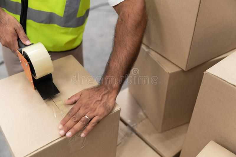Male worker packing cardboard box with tape gun dispenser in warehouse. Close-up of male worker packing cardboard box with tape gun dispenser in warehouse. This stock photo