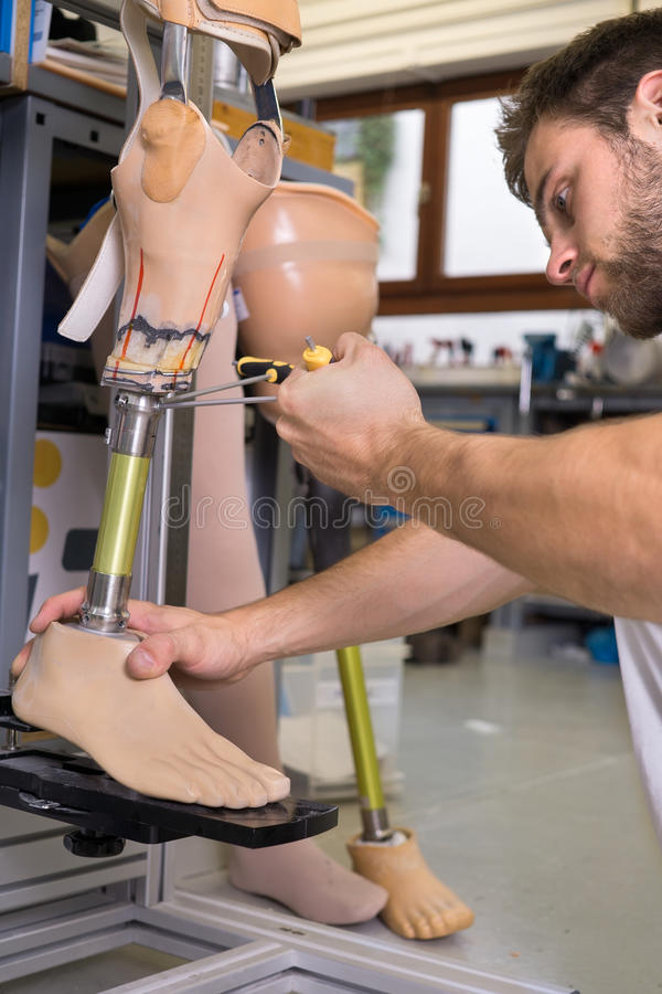 Close up of man adjusting false limb. Close up on single adult technician using special tool to adjust length on prosthetic false limb assembly in workshop royalty free stock images