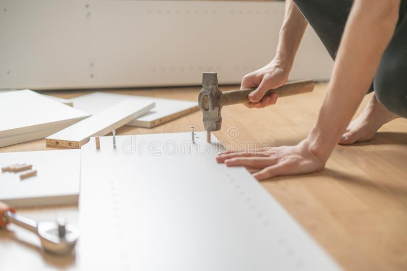 Close up man assembling brand new furniture with the hammer on the wooden floor n royalty free stock photography