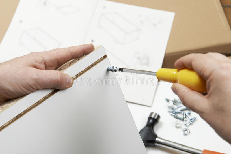 Close Up Of Man Assembling Flat Pack Furniture With Screwdriver stock photos