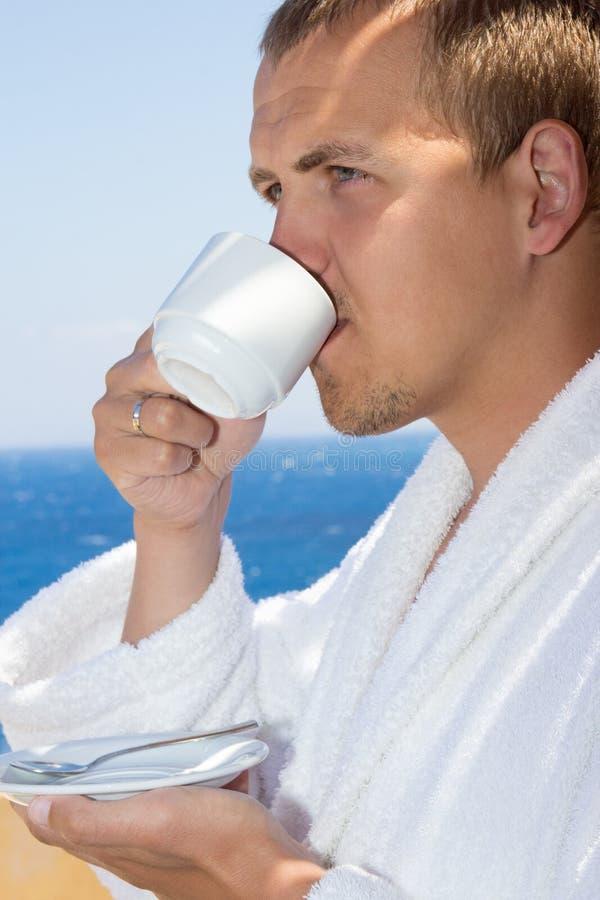 Close up of man in bathrobe drinking coffee on balcony stock photos