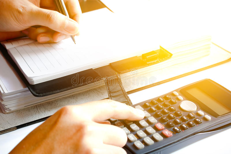 Close up of man with calculator counting making notes at home, h. And is writes in a notebook with books, soft focus royalty free stock photos