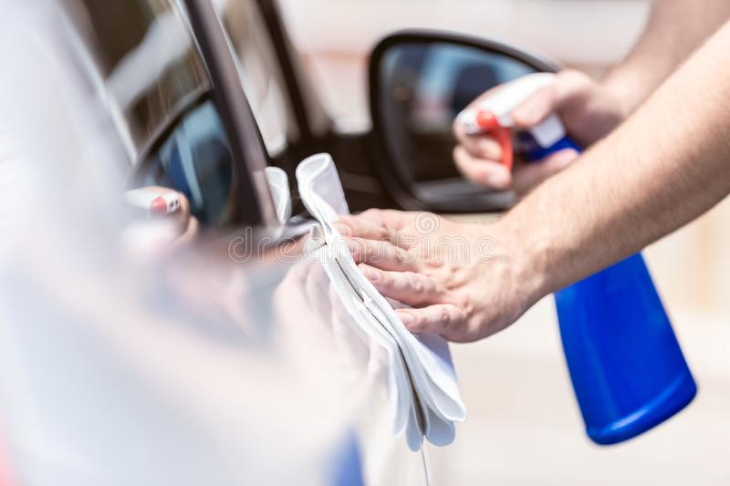 Man hands cleaning and spaying car exterior royalty free stock images